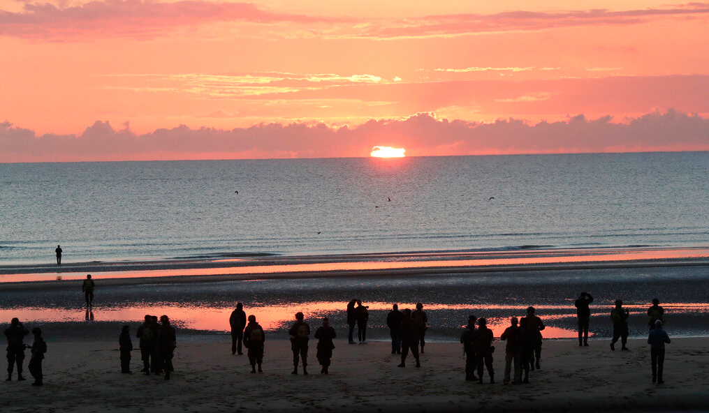 World War II re-enactors gather at dawn on Omaha Beach, in Normandy, France, Thursday, June 6, 2019 during commemorations of the 75th anniversary of D-Day.