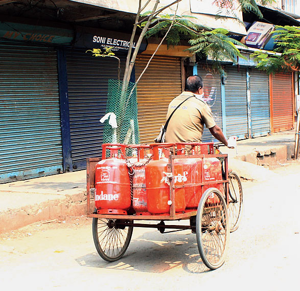 A delivery man carries LPG cylinders in Guwahati on Friday.