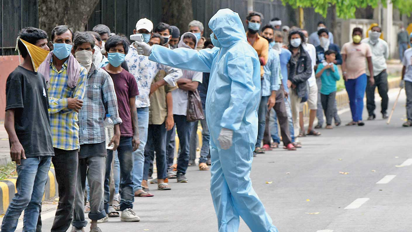 A member of the National Students' Union of India checks the temperature of people who have come to collect food at its office on Raisina Road in New Delhi on Monday.