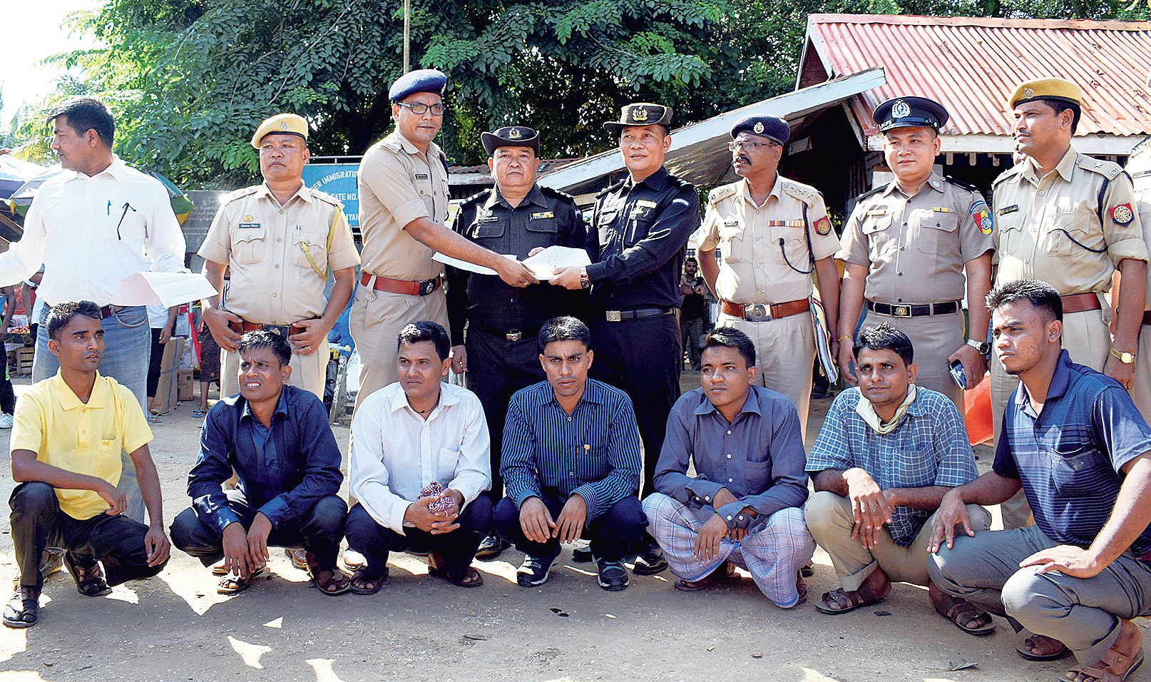 The seven Rohingya men sit as Indian and Myanmar security officials exchange documents before their deportation at Moreh, Manipur, on Thursday.