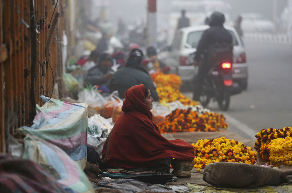 A flower vendor warms herself with a traditional Kashmiri fire pot on a cold and foggy morning in Jammu