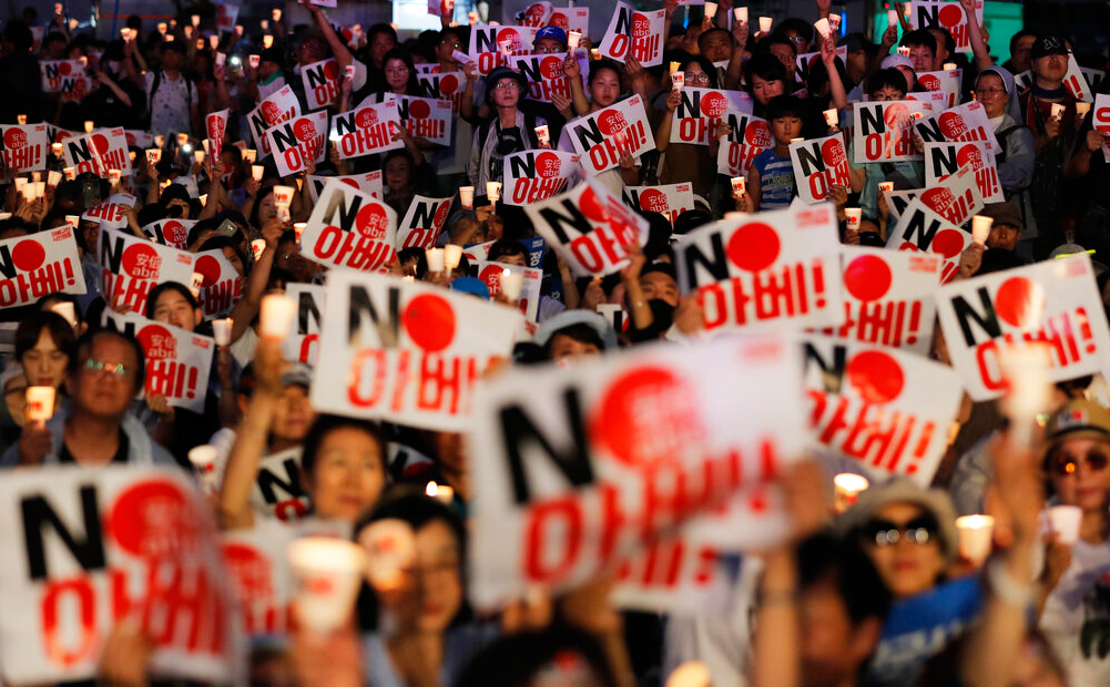 Protesters hold candles and signs during a rally denouncing Japanese prime minister Shinzo Abe and demanding an end to the General Security of Military Information Agreement, a military intelligence-sharing pact with Japan, in Seoul on Thursday, August 15, 2019