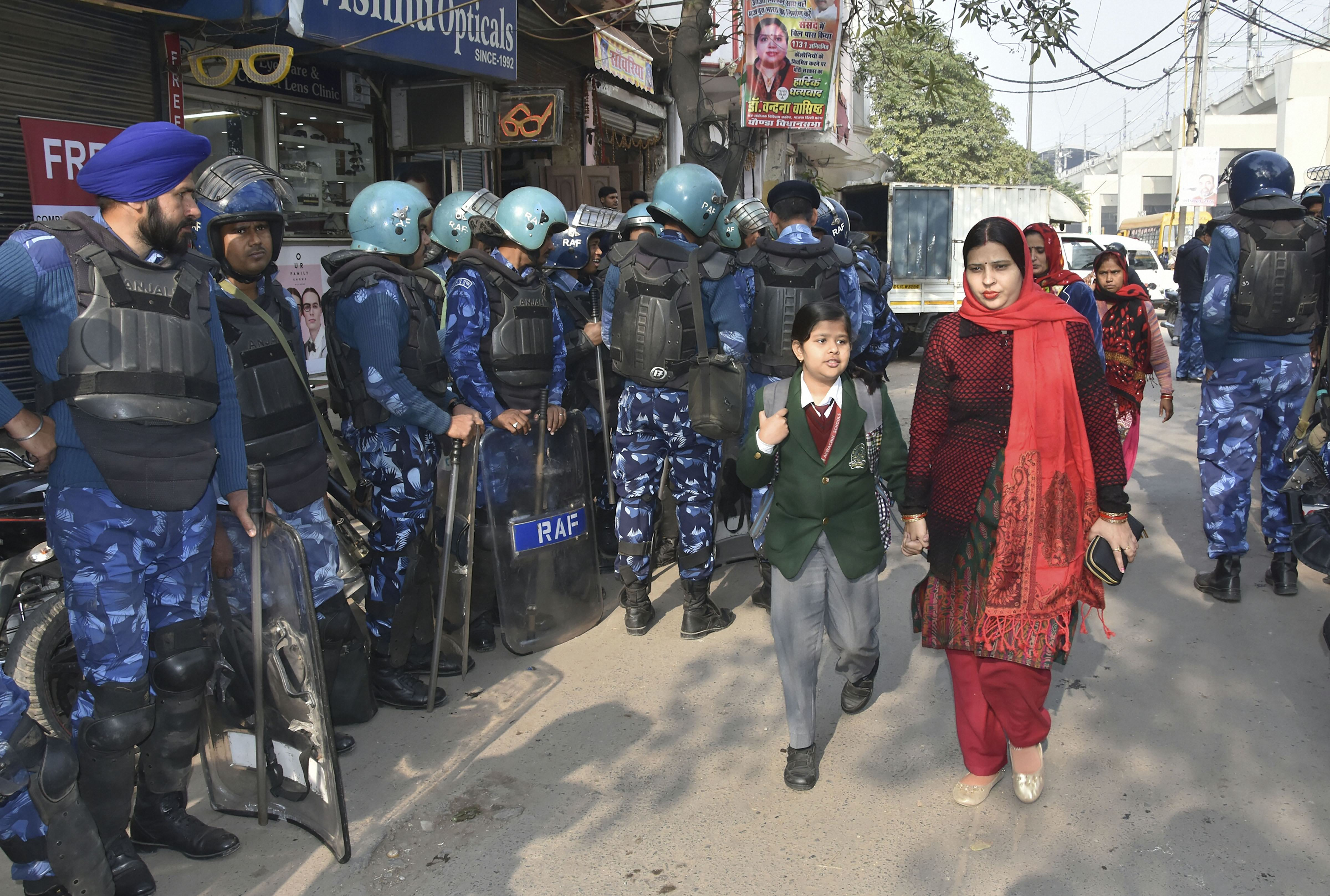 RAF personnel keep vigil as women and a child walk past them at violence-hit Jafarabad in New Delhi, Wednesday, December 18, 2019