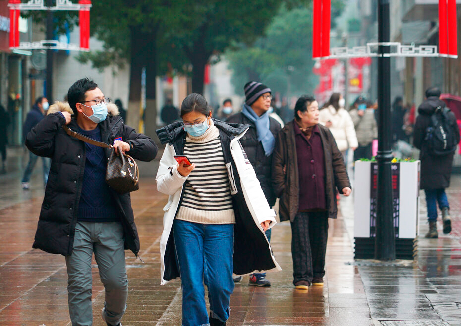 Masked pedestrians walk down a shopping street in downtown Wuhan, China, Wednesday, January 22, 2020.