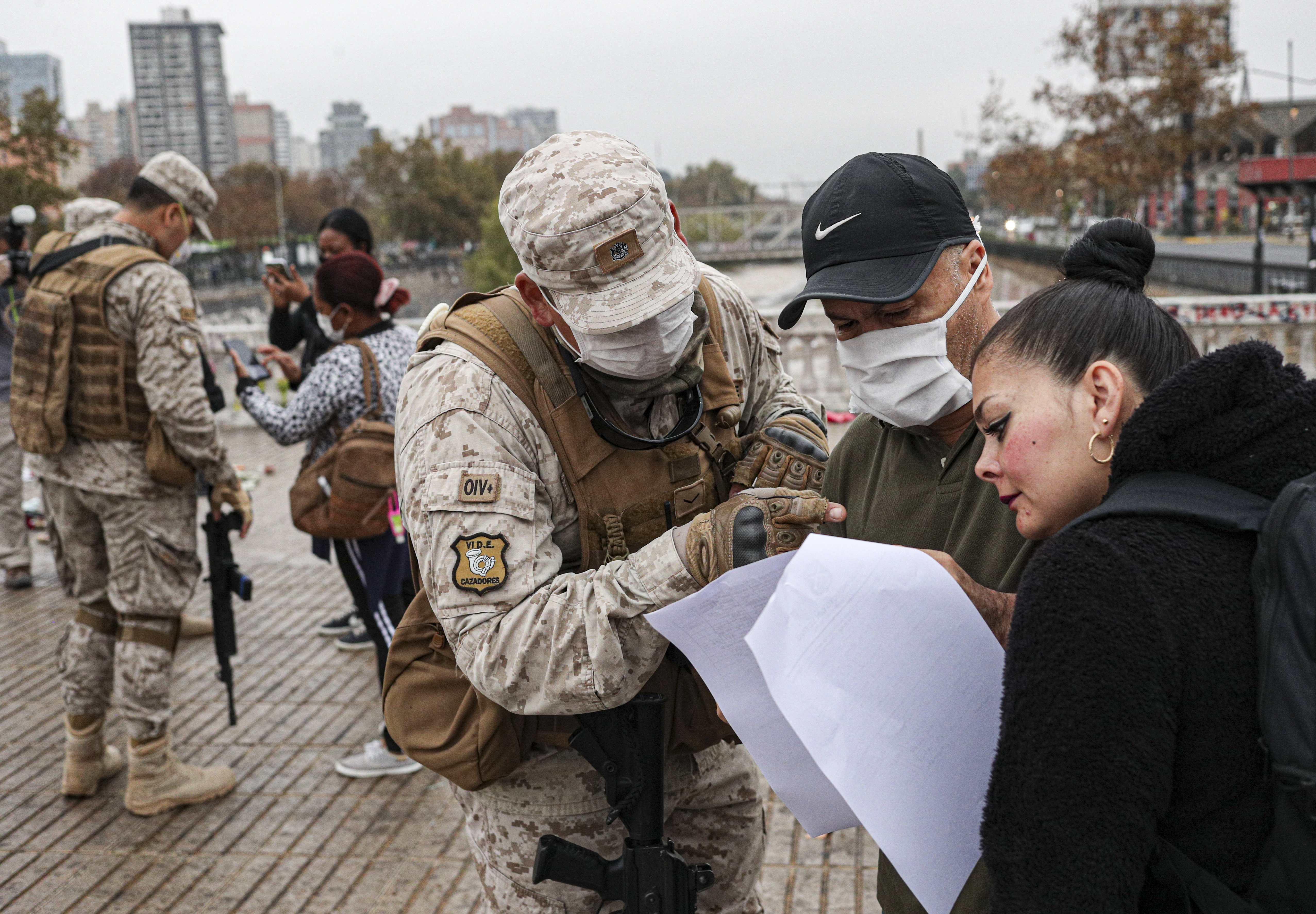 A soldier looks for names on a letter that gives people permission to be in transit, at a checkpoint that monitors the entry of people at the city limit of Santiago, Chile