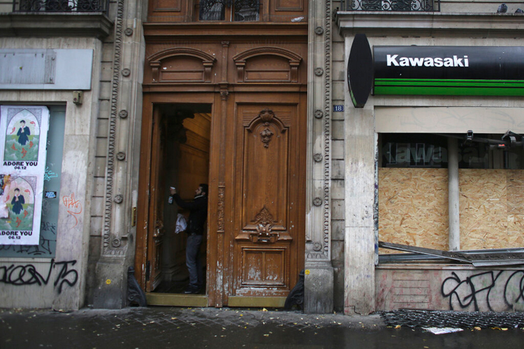 A man cleans a door in Paris on December 6, a day after the city witnessed widespread violence