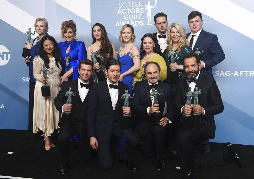Jane Lynch, from top left, Stephanie Hsu, Carolina Aaron, Marin Hinkle, Rachel Brosnahan, Alex Borstein, Luke Kirby, Matilda Szydagis, and Sean Tarantina. Joel Johnstone, from bottom left, Michael Zegen, Kevin Pollak, and Tony Shalhoub pose in the press room with the award for outstanding performance by an ensemble in a comedy series for