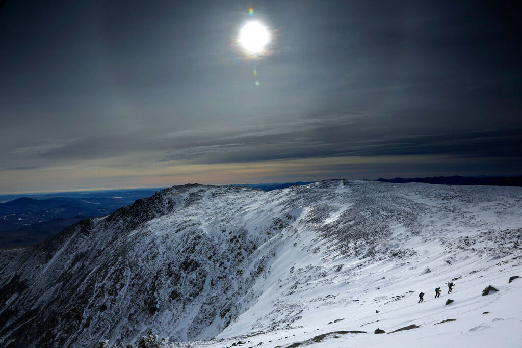 Under a midday winter solstice sun, a trio of climbers make their way up a slope on Mount Washington on Saturday.