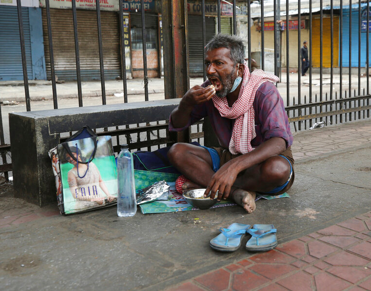 A homeless man eats food given by volunteers during lockdown in Bangalore, Friday, April 24, 2020.