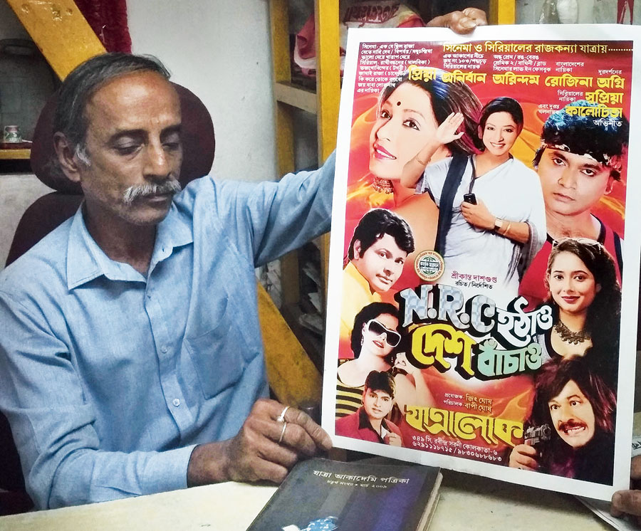 """Khokon Porel, manager of theatre group Anandalok, holds up a poster of """"NRC Hatao, Desh Bachao (Repeal NRC, Save the Country)"""" on Thursday."""