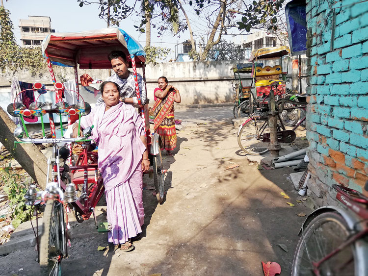 Ajmeri Khatun with her son and some of the rickshaws she has acquired over the years
