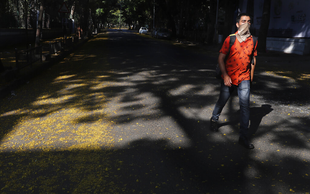 A man covers his face with a handkerchief and walks on an empty street during a lockdown in Mumbainon Friday, April 17