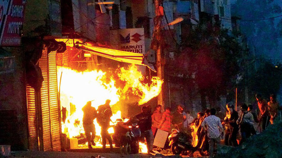 Rioters set ablaze a shop in northeast Delhi on February 25.
