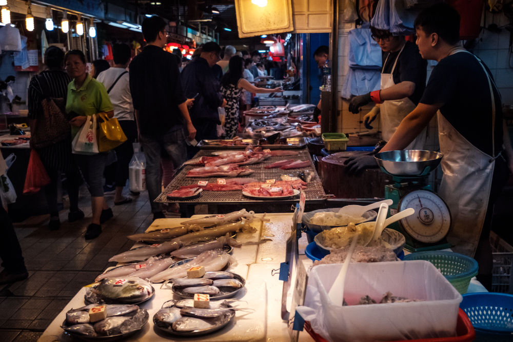 Vendor preparing fish at a wet market in HongKong, China.
