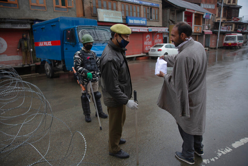 A man shows his prescription and pleads to a policeman to let him pass a check point hoping to buy medicines in Srinagar on March 27