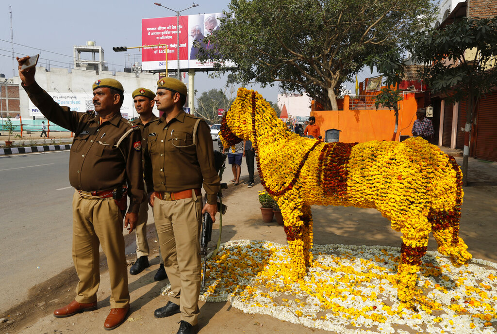 Policemen take a selfie on a street decorated with floral arrangements in Agra, on Monday