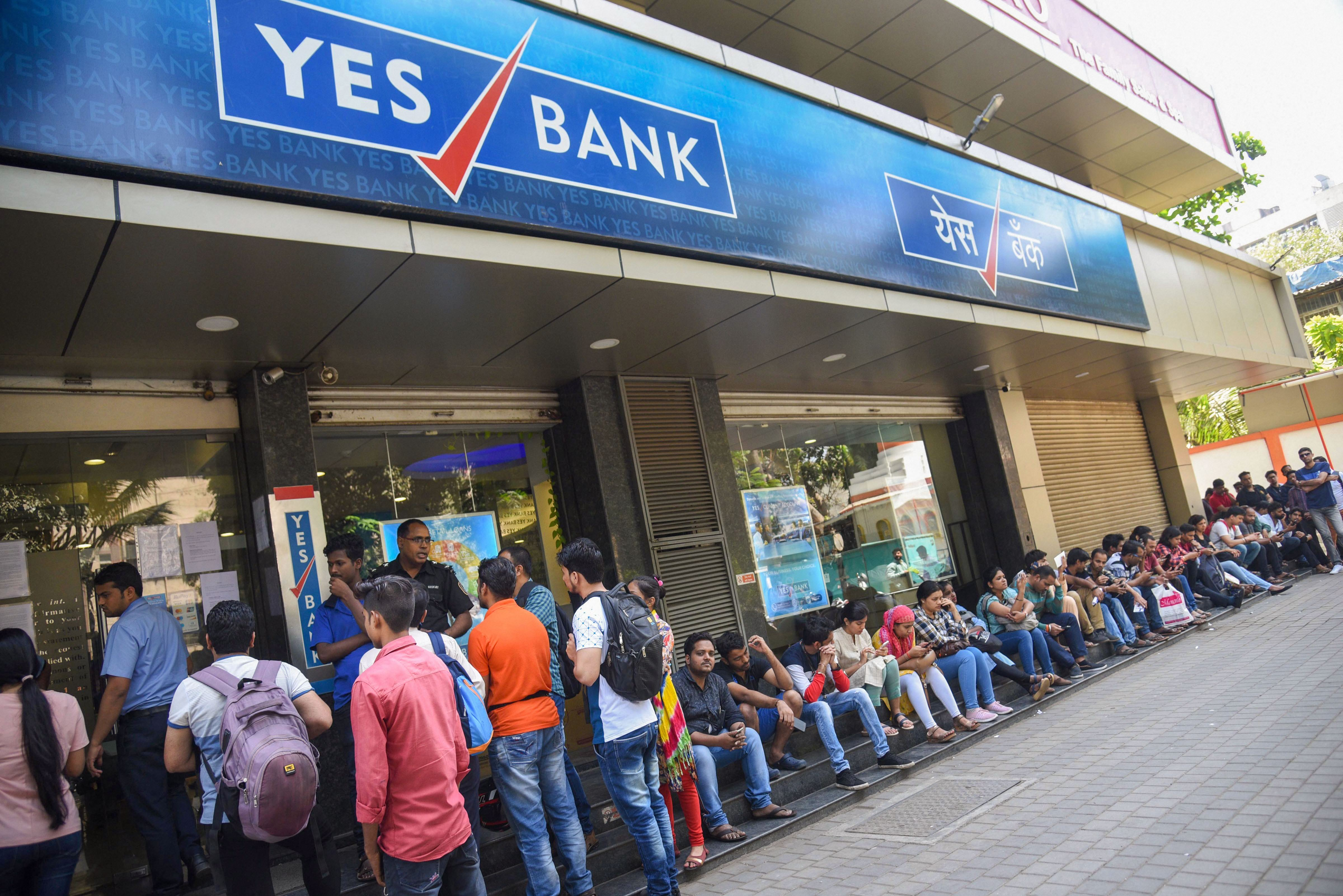 Account holders queue up outside Yes Bank to withdraw money, in Mumbai, Saturday, March 7, 2020