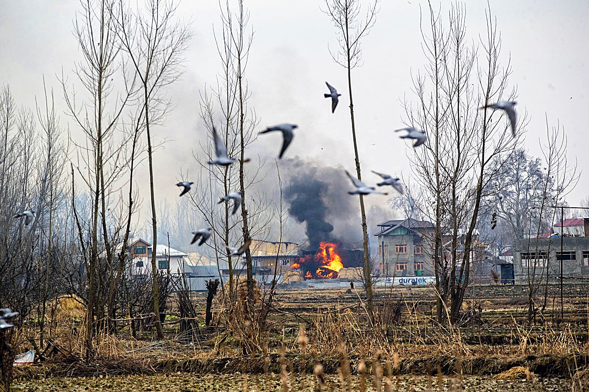 Flames and smoke billow from a house where militants are suspected to have taken refuge in Pulwama on  February 18, 2019.
