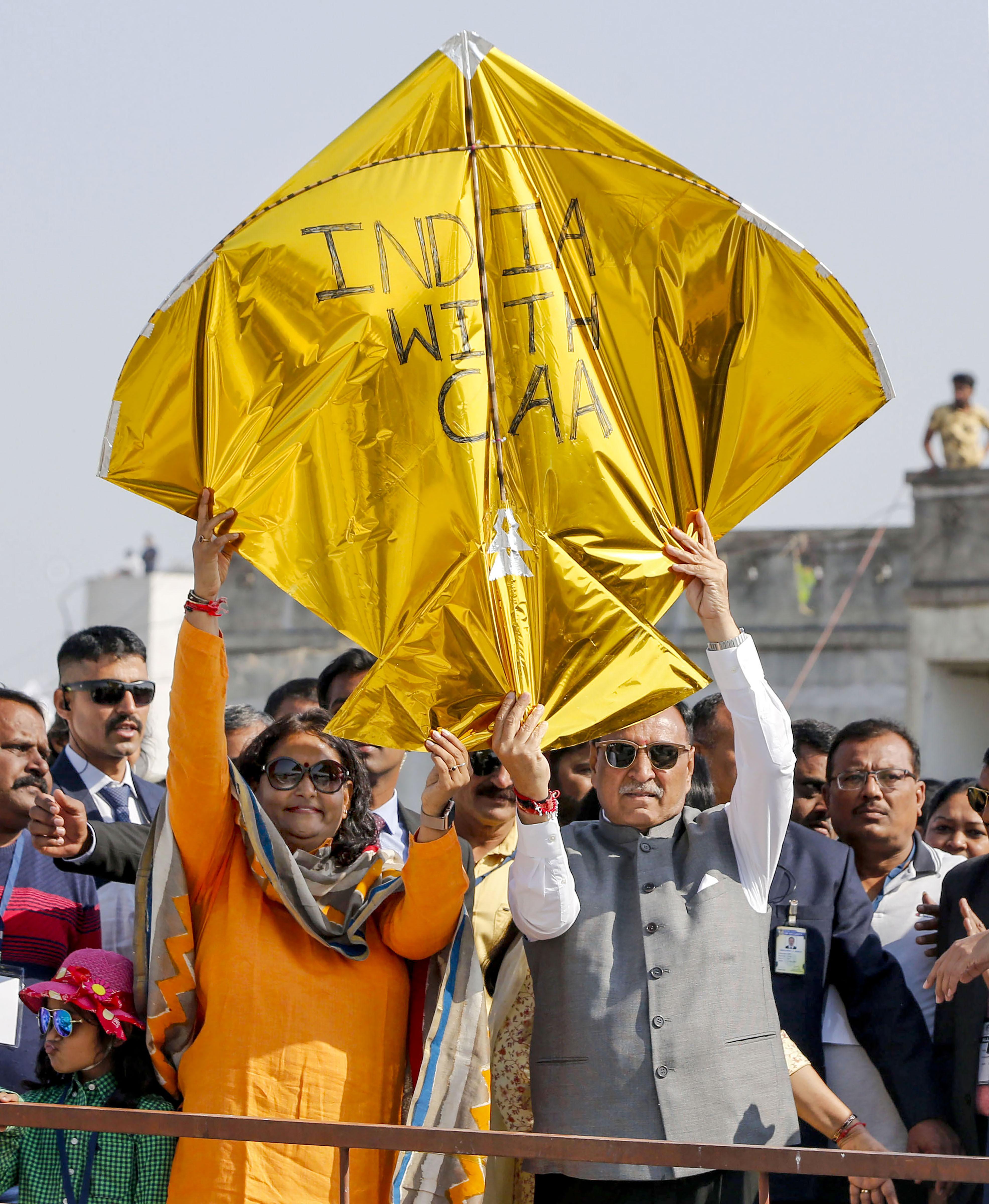 Gujarat chief minster Vijay Rupani holds a kite with message