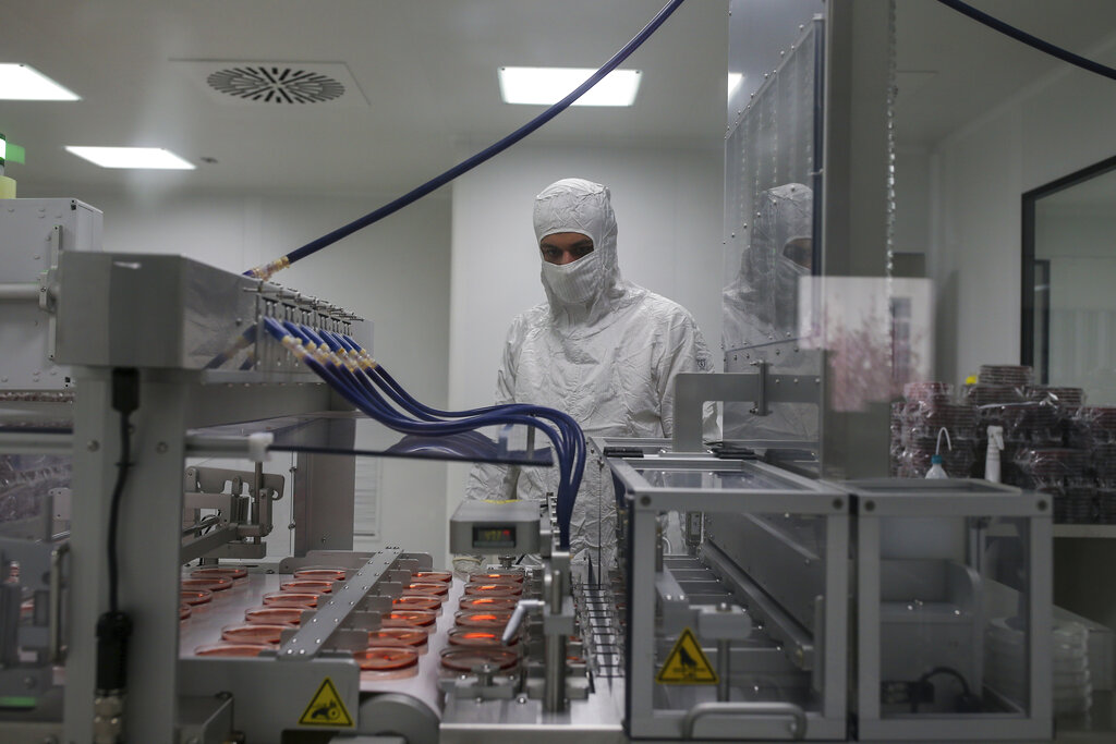 Wearing a protective suit, a research and development company worker oversees the production of coronavirus testing kits in Gebze, northwestern Turkey, Monday, March 23, 2020.