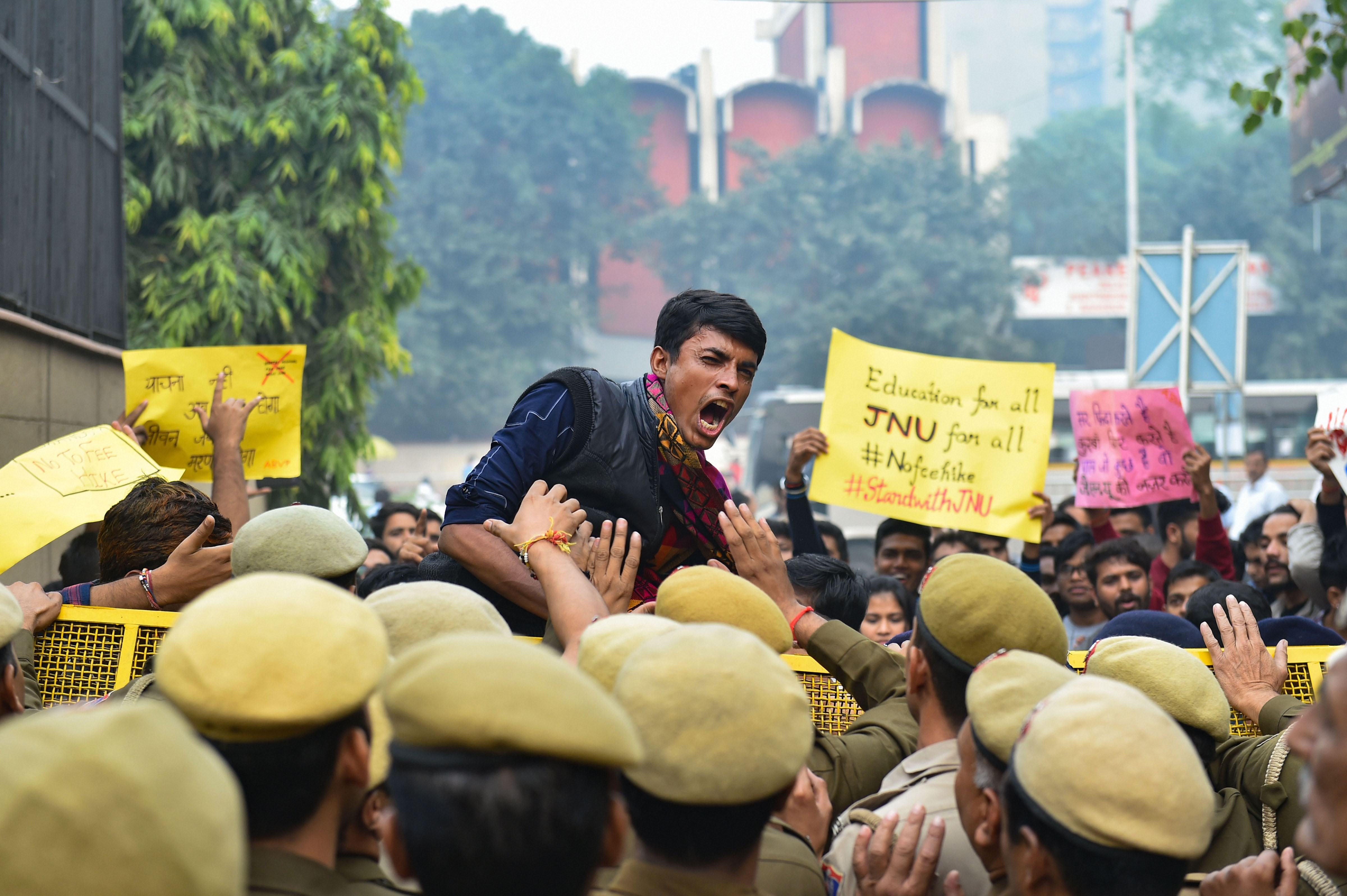 Police stop JNU students who were staging a protest over the hostel fee hike outside the UGC office at ITO in New Delhi, Wednesday, Nov. 13, 2019.