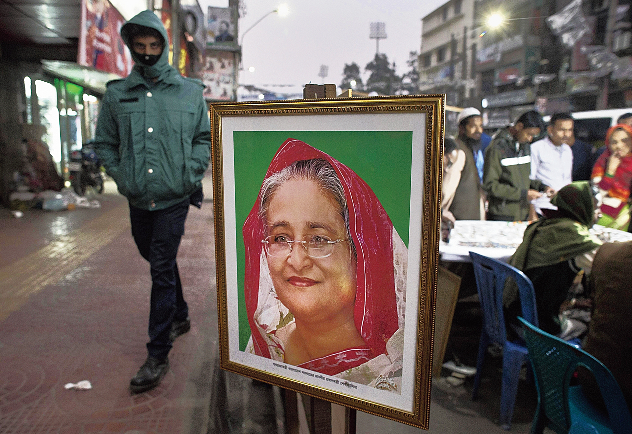 A man walks past a portrait of Sheikh Hasina on sale at a roadside shop in Dhaka.