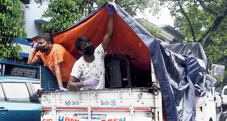 Men on a mini-truck hold a tarpaulin sheet for cover during the rain on SP Mukherjee Road on Monday.