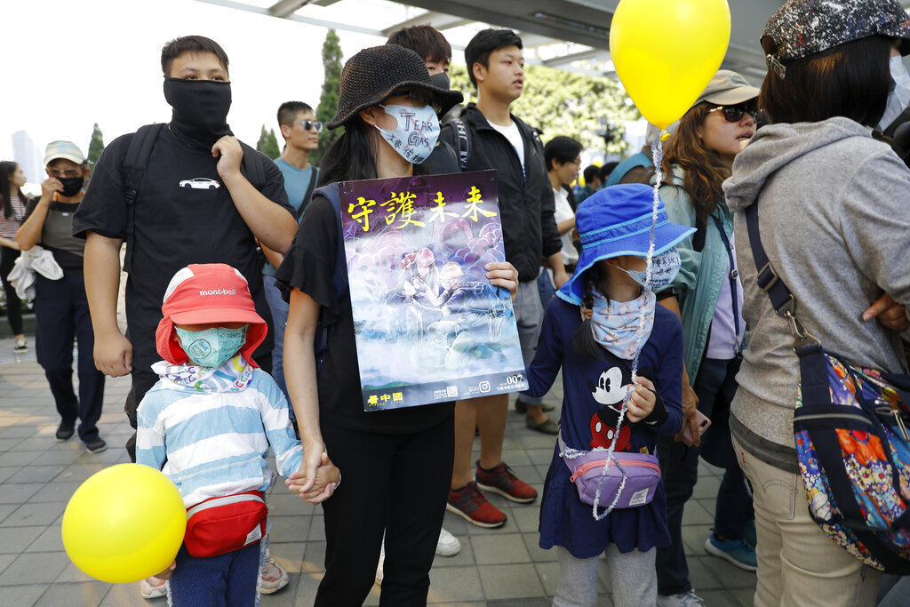 A masked woman and children hold a balloon and a placard which reads