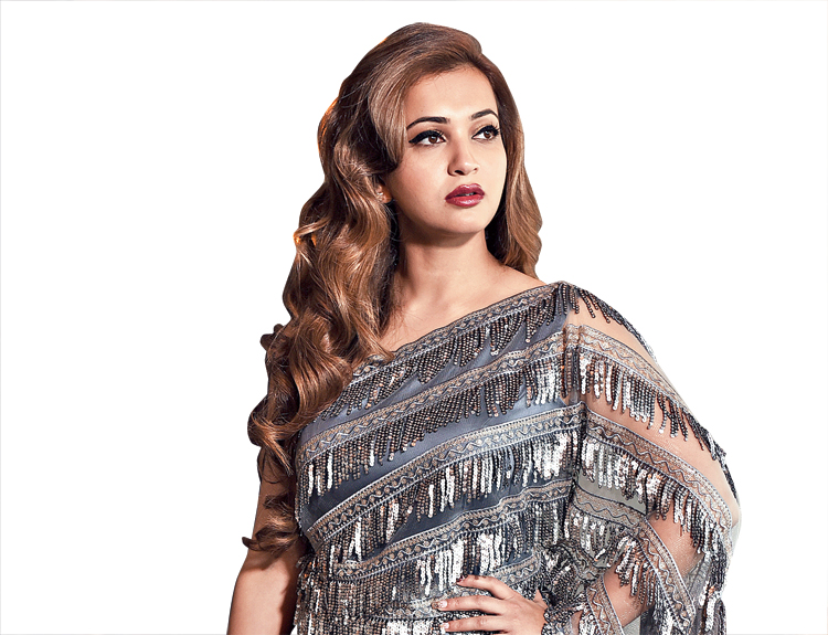 "This ""concept sari"" is an ideal pick if you want to go glam at a winter wedding. The one-piece sari in a metallic silver tone with a light satin drape on the lower part and a net pallu embroidered with silver sequinned tassels is smart and chic. ""The Jyotee Khaitan 'concept sari' is back again and has become the 'big thing' this season and is here to stay! This occasionwear concept sari can be worn to a Christmas cocktail party as well,"" said Jyotee. ""This draped sari is apt for a Sangeet party,"" said Koushani."