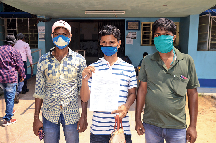 The three villagers from Hooghly's Goghat with their application in front of the office of the SDO, Arambagh, on Monday.