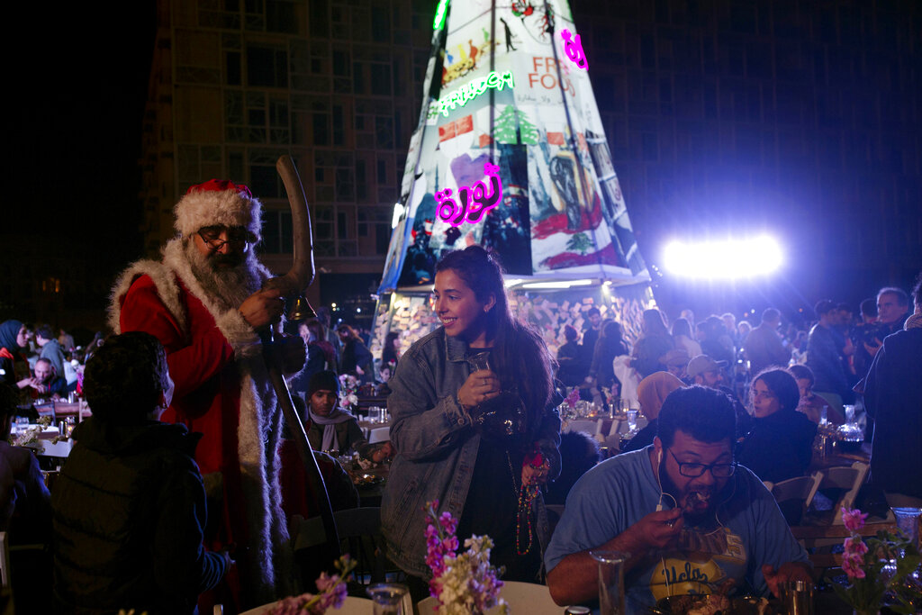 A volunteer, centre, serves drinks at a public Christmas dinner as a boy asks Santa Claus for a selfie, in Martyrs Square where anti-government activists are encamped, in Beirut, Lebanon. As Lebanon's protest movement enters its third month, the economic pinch is hurting everyone. But Lebanese are resorting to what they've done in previous wars and crises: They rely on each other, not the state.
