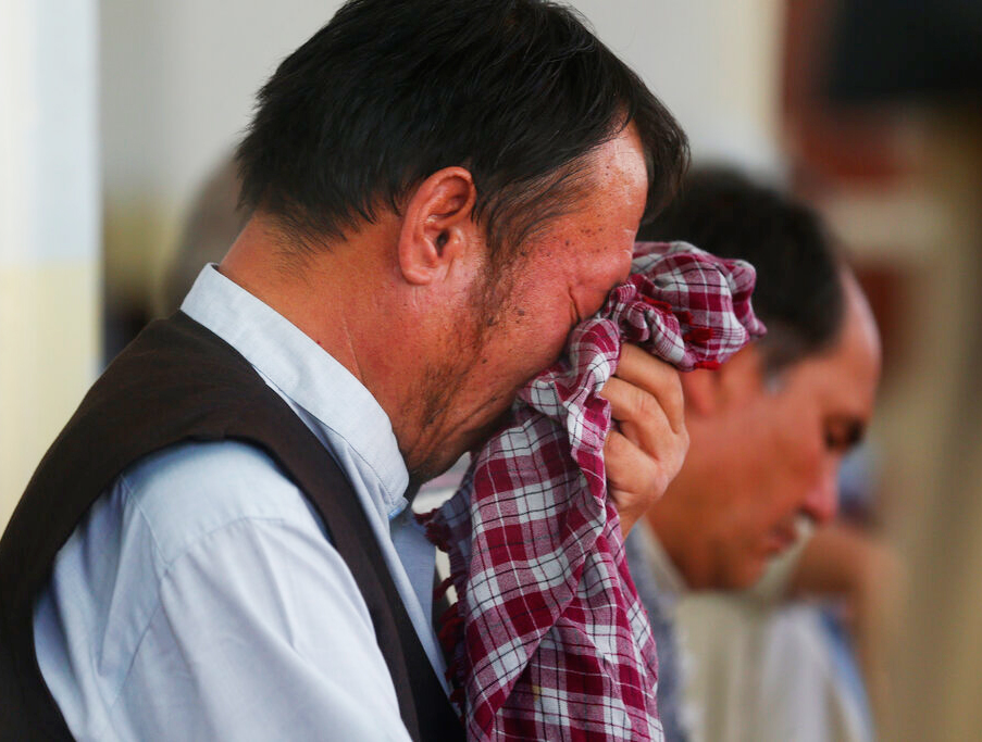 Men mourn at a memorial service for the victims of the wedding hall attack, in Kabul on Tuesday, August 20, 2019. This attack came at a time when the US and the Taliban were closing in on a deal to reduce US military presence in Afghanistan, hoping to build a road map to a ceasefire.