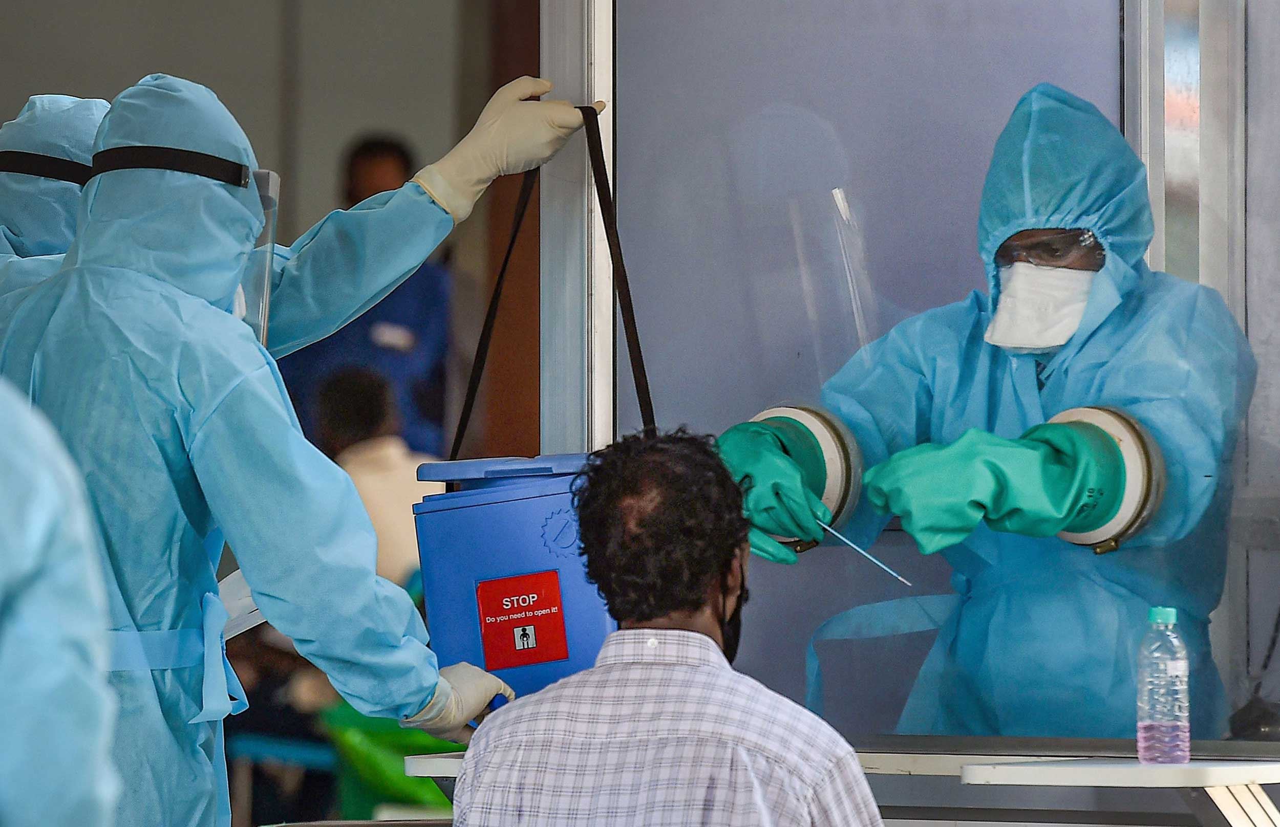 A medic takes samples from a man arriving from Myanmar at Anna International Airport in Chennai on Sunday.