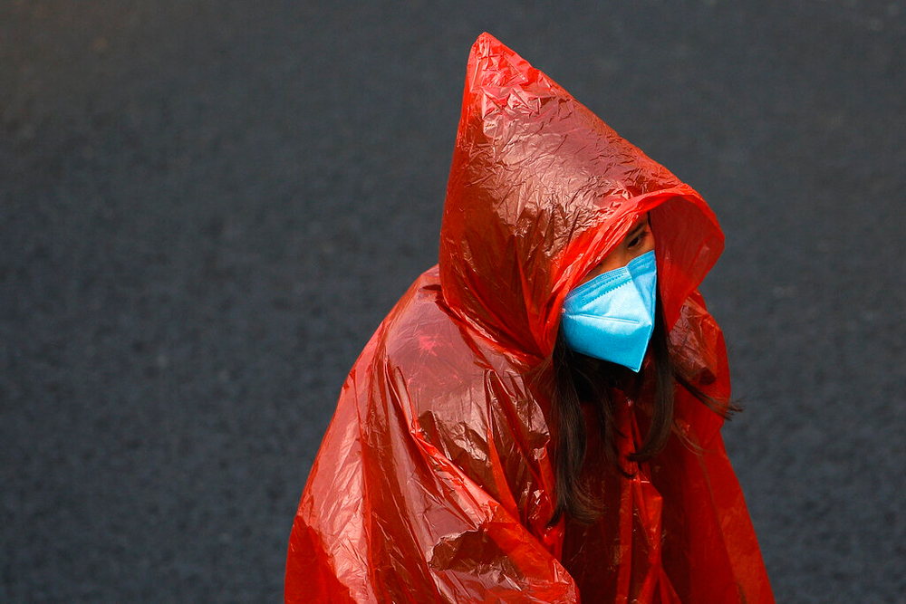 A masked woman in a plastic raincoat in Beijing on Tuesday