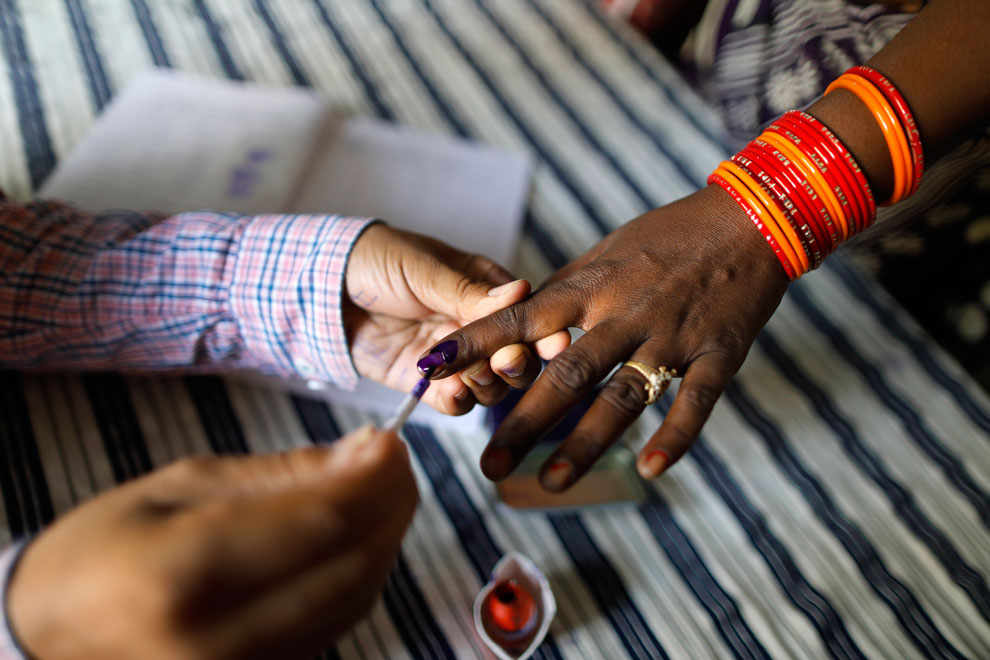 A polling officer puts indelible ink mark on the index finger of a voter at a polling station, on the outskirts of Varanasi on Sunday, May 19, 2019