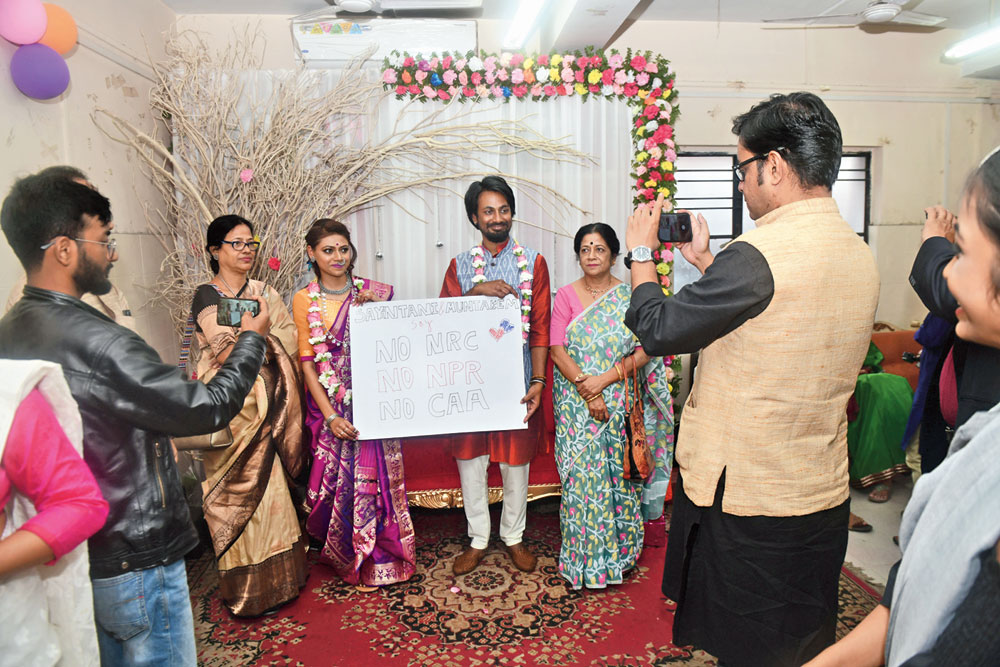 Film-makers Sayantani Khan and Muntakem Haque hold a poster opposing the Citizenship (Amendment) Act, National Register of Citizens and the National Population Register at their wedding reception on Sunday.