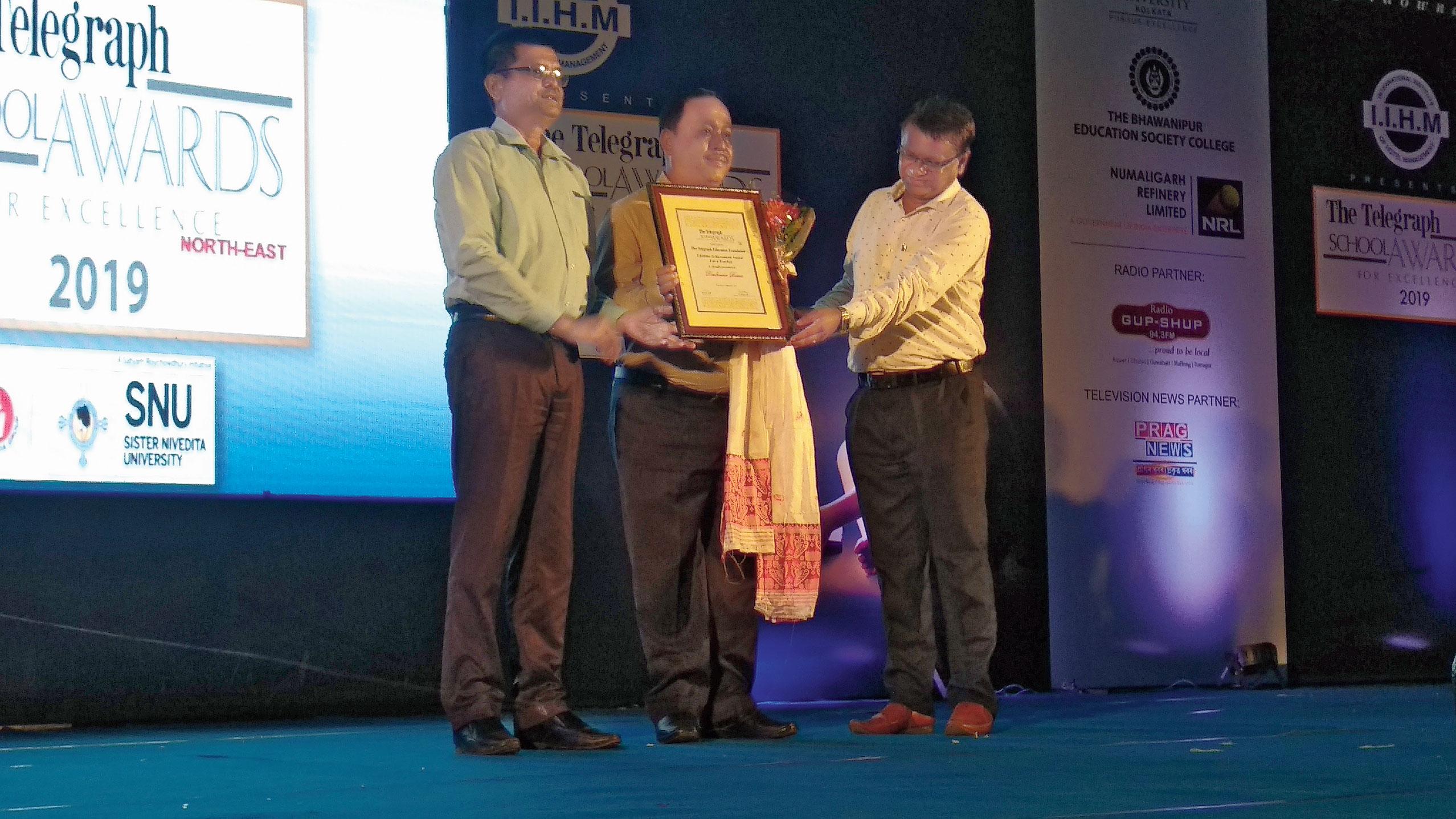 Dimbeswar Baruah's son Moni Baruah (centre) receives the award.