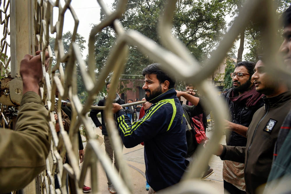 Jamia Millia Islamia students try to break a lock during the protest in New Delhi on Monday