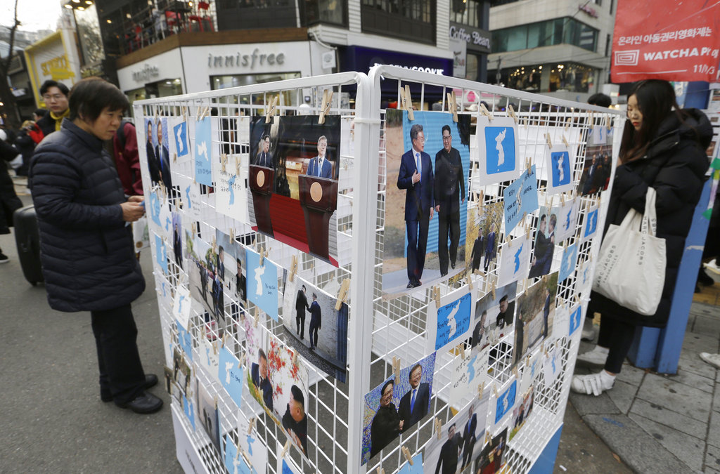 In this November 25, 2018, file photo, photos of Moon Jae-in and Kim Jong-un and unification flags are displayed during a campaign to welcome Kim's possible visit to South Korea.