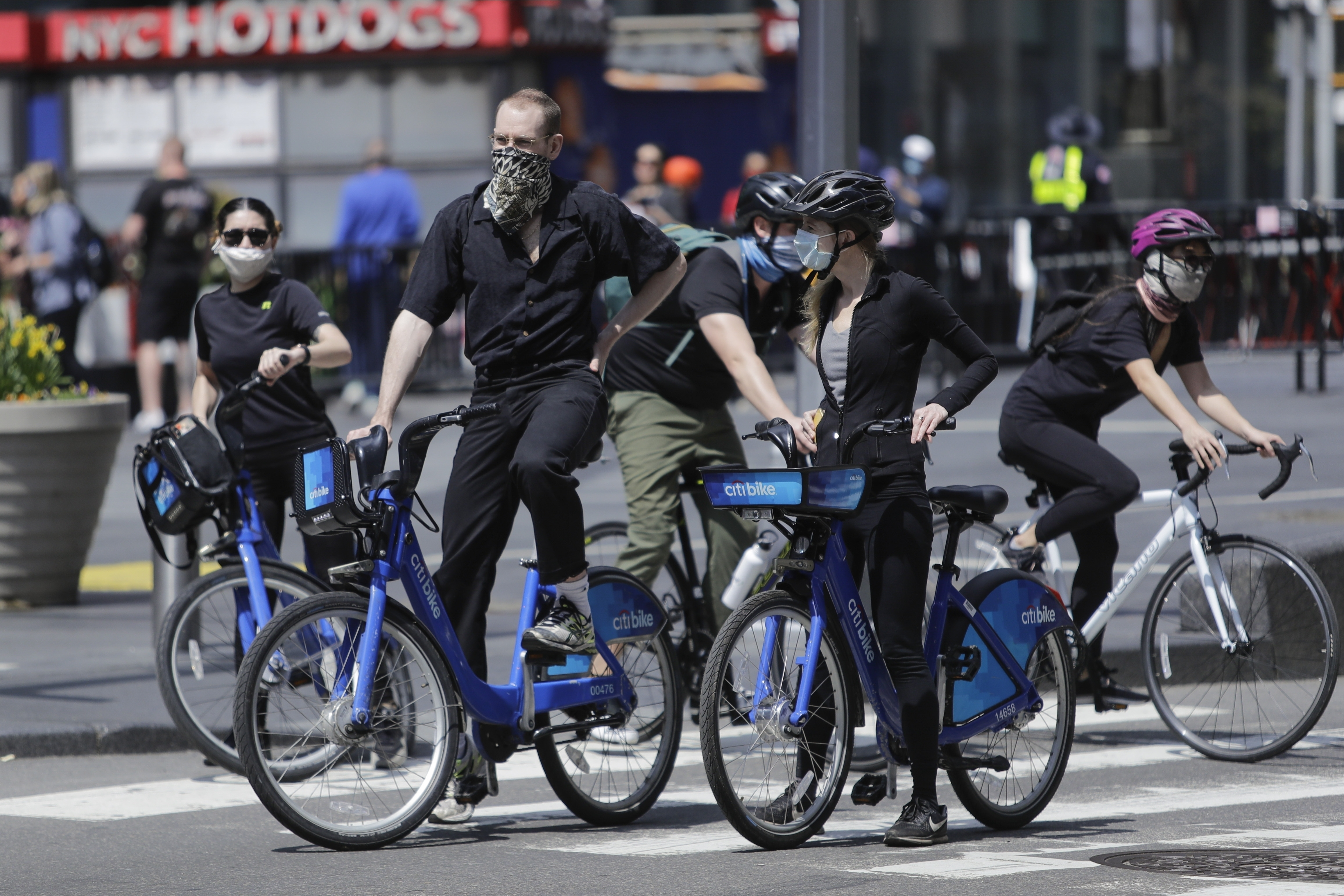 Cyclists wearing protective masks ride through Times Square