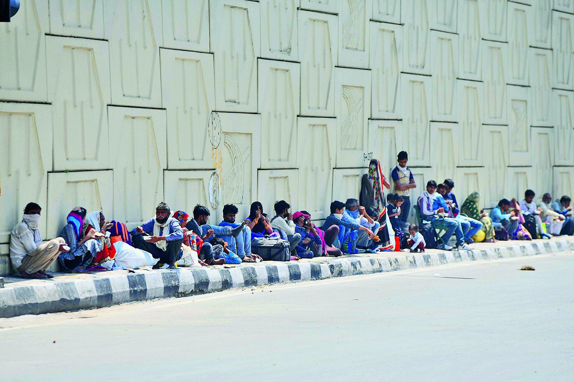 Migrants wait  on Wednesday at the Delhi-Uttar Pradesh border for transport to reach home.