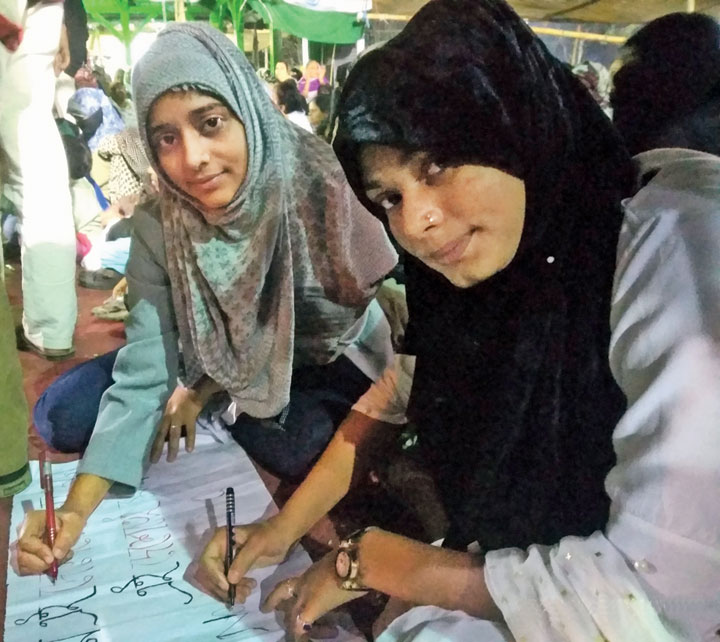 Shamreen Parvez from Rajabazar and (right) Neha Parveen from Topsia write their poster