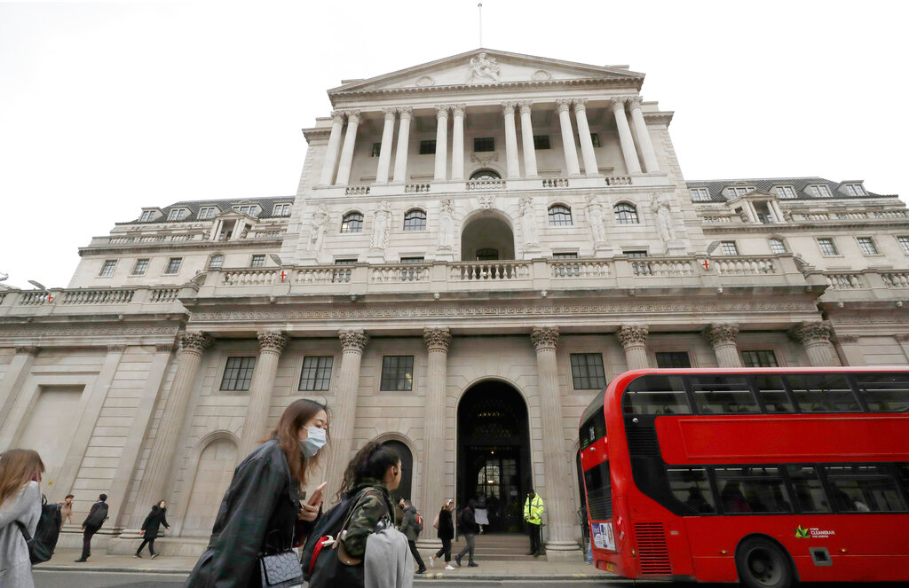 In this file photo dated Wednesday, March 11, 2020, Pedestrians wearing face masks pass the Bank of England in London. In forecasts published Thursday May 7, 2020,