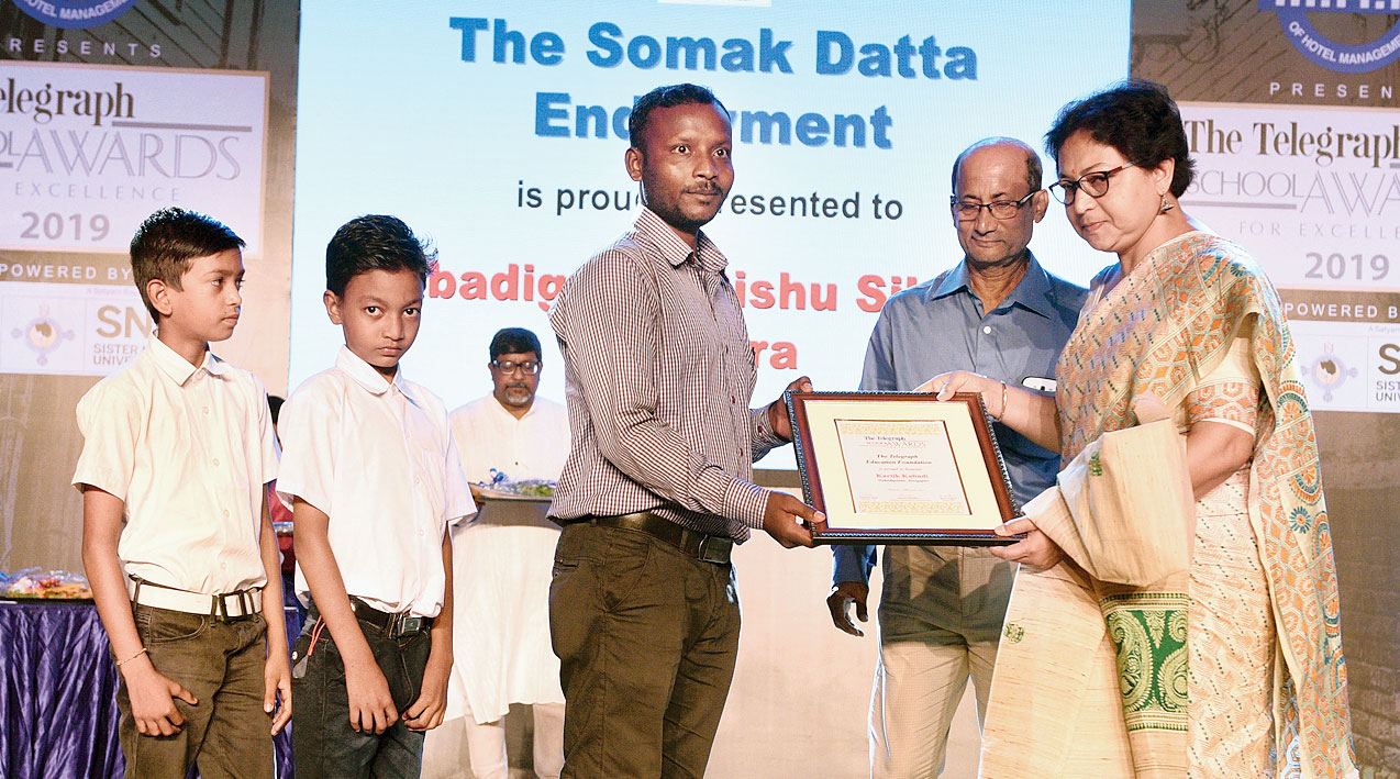 Gourisankar and Sujata Datta, parents of Somak Datta, hands over the certificate to Kartick Kalindi on Saturday.