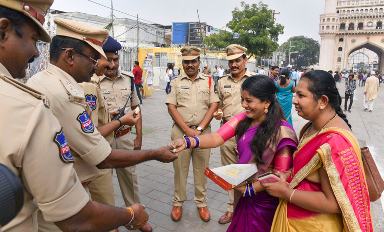 Women offer sweet to policemen in Hyderabad on Friday