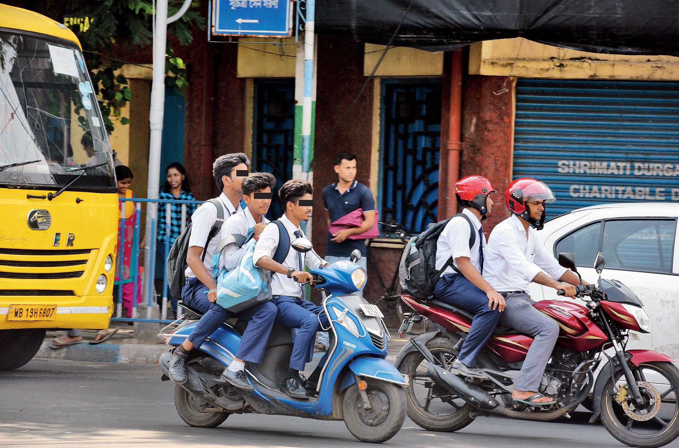 Three boys in school uniform ride a two-wheeler without helmets near Ballygunge Dhaba.