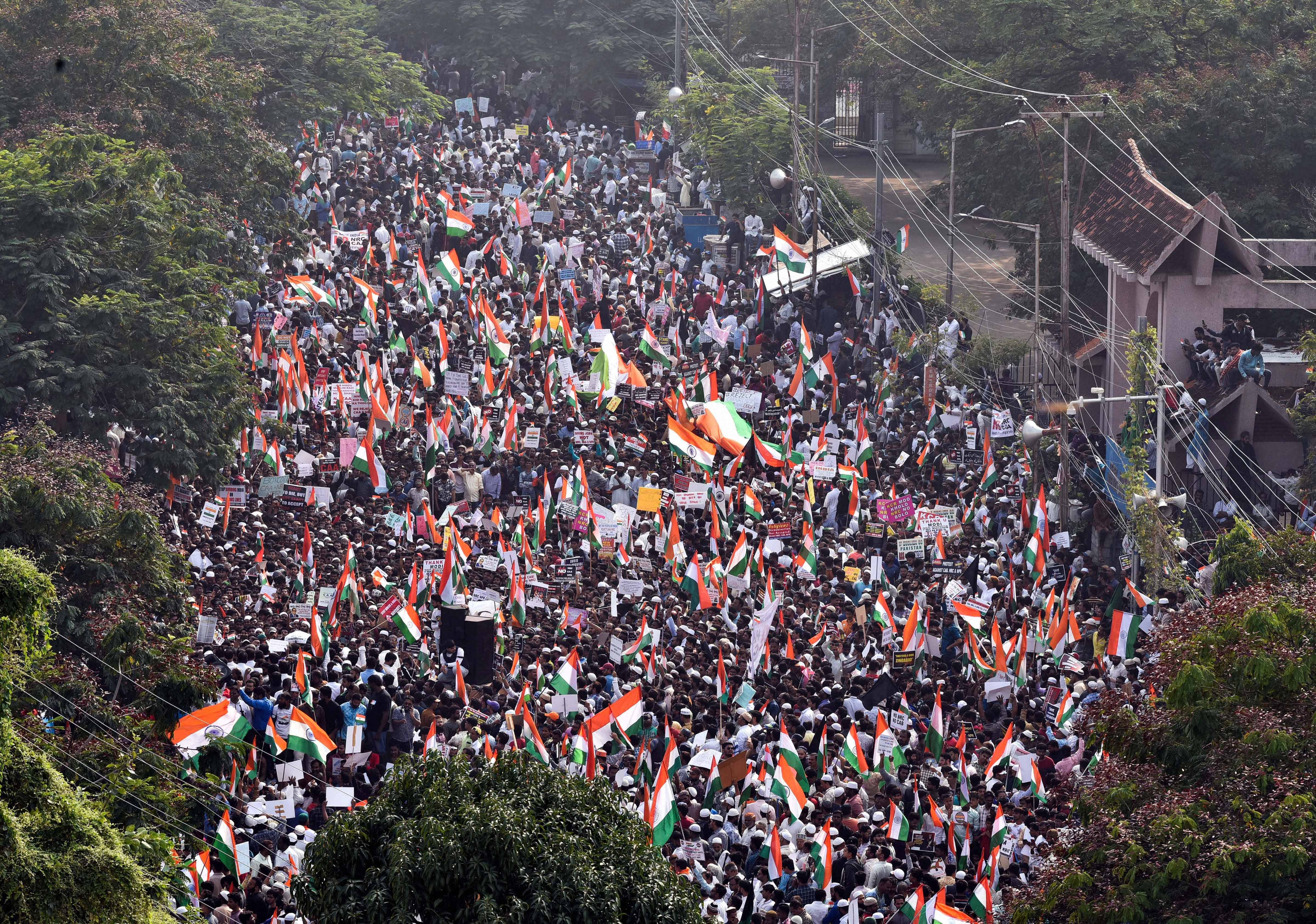 Protestors wave Indian Tri-colours during a demonstration against the amended Citizenship Act, NRC and NPR at Indira Park in Hyderabad, Saturday, January 4, 2020.