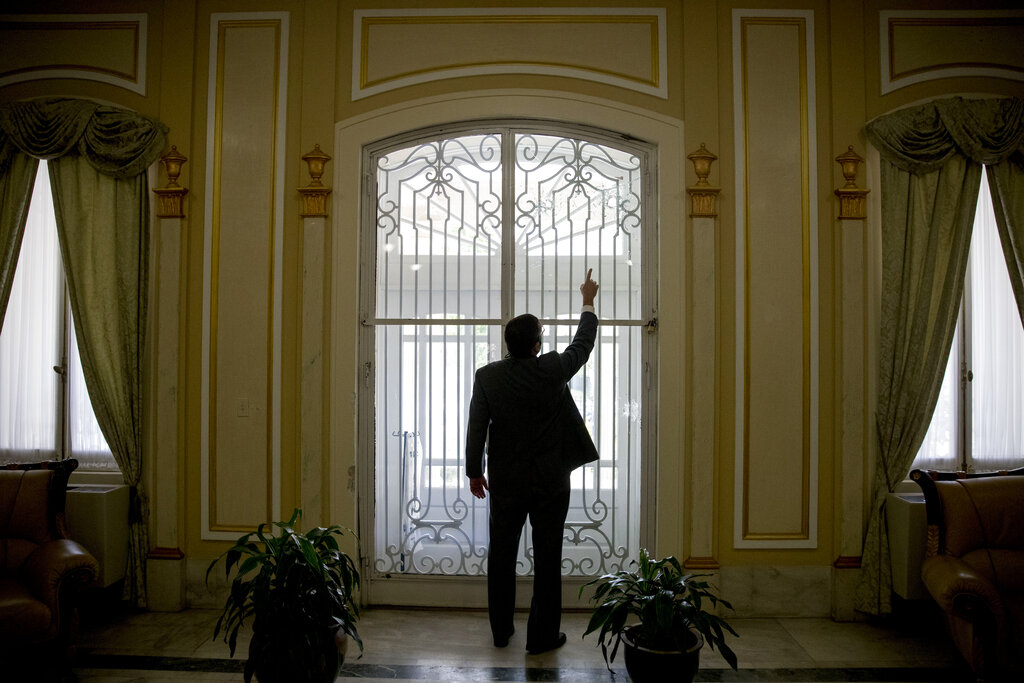 Cuba's Ambassador to the United States Jose Ramon Cabanas points out bullet holes in the main entrance after a man opened fire early Thursday morning at the Cuban Embassy, Friday, May 1, 2020, in Washington. Officers found the suspect with an assault rifle and took the person into custody without incident, police said.