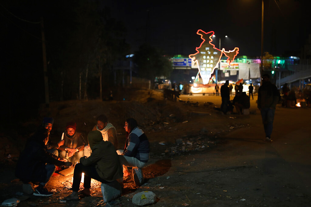 Activists keep themselves warm around a bonfire near the protest site in New Delhi's Shaheen Bagh on Thursday