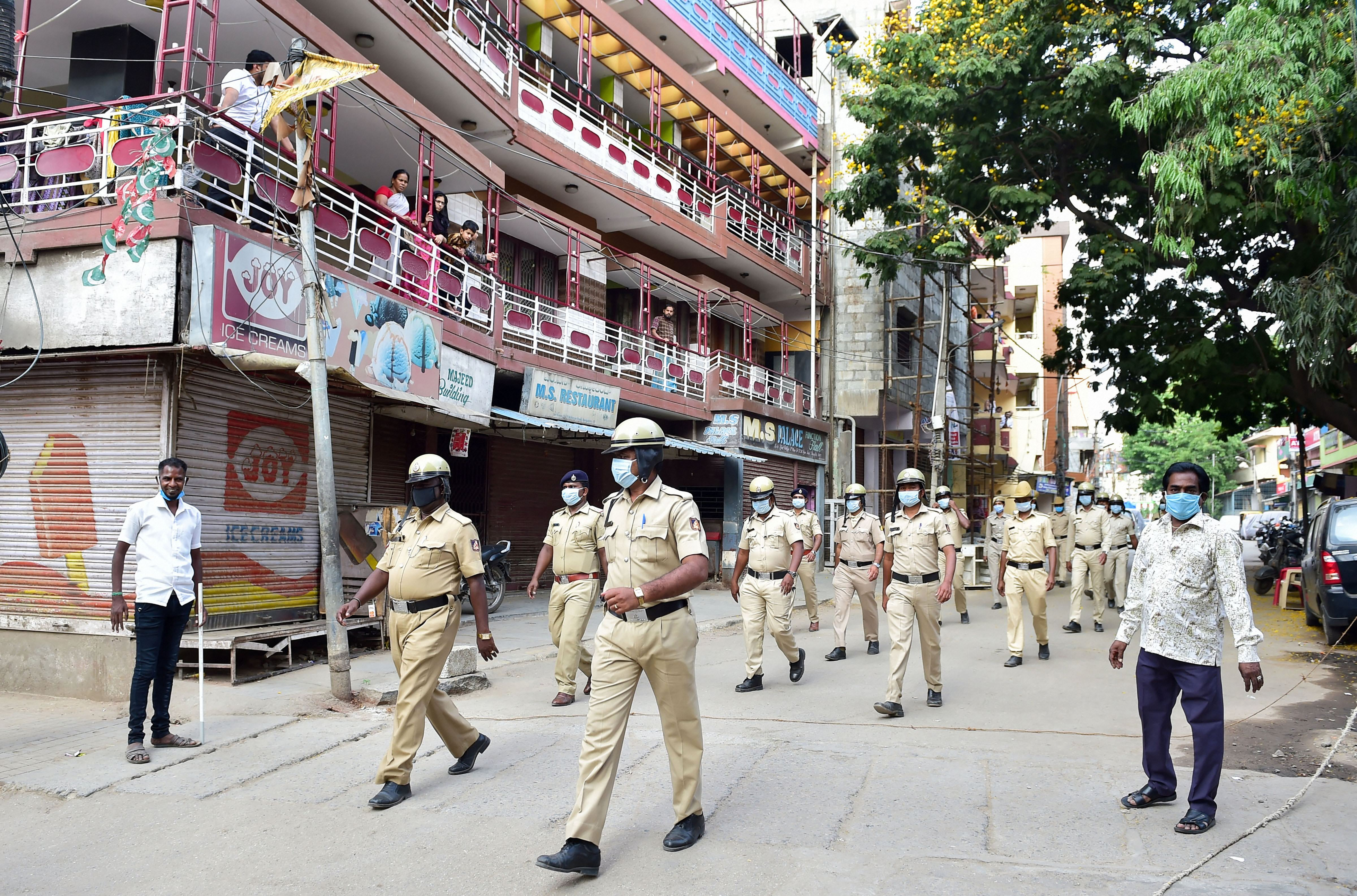 Police personnel conduct a flag march to urge citizens to stay at home during a nationwide lockdown, imposed in the wake of novel coronavirus pandemic, in Bengaluru, Sunday, April 5, 2020
